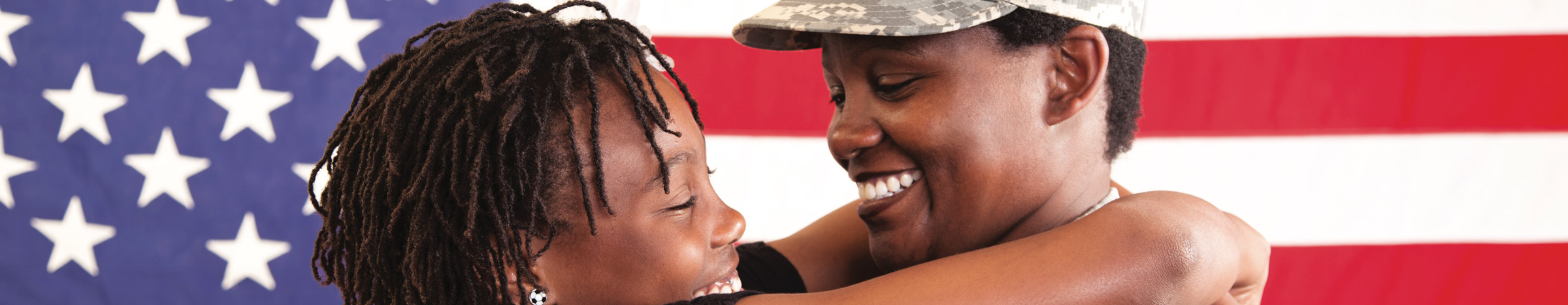Veteran woman hugs girl in front of the American flag.
