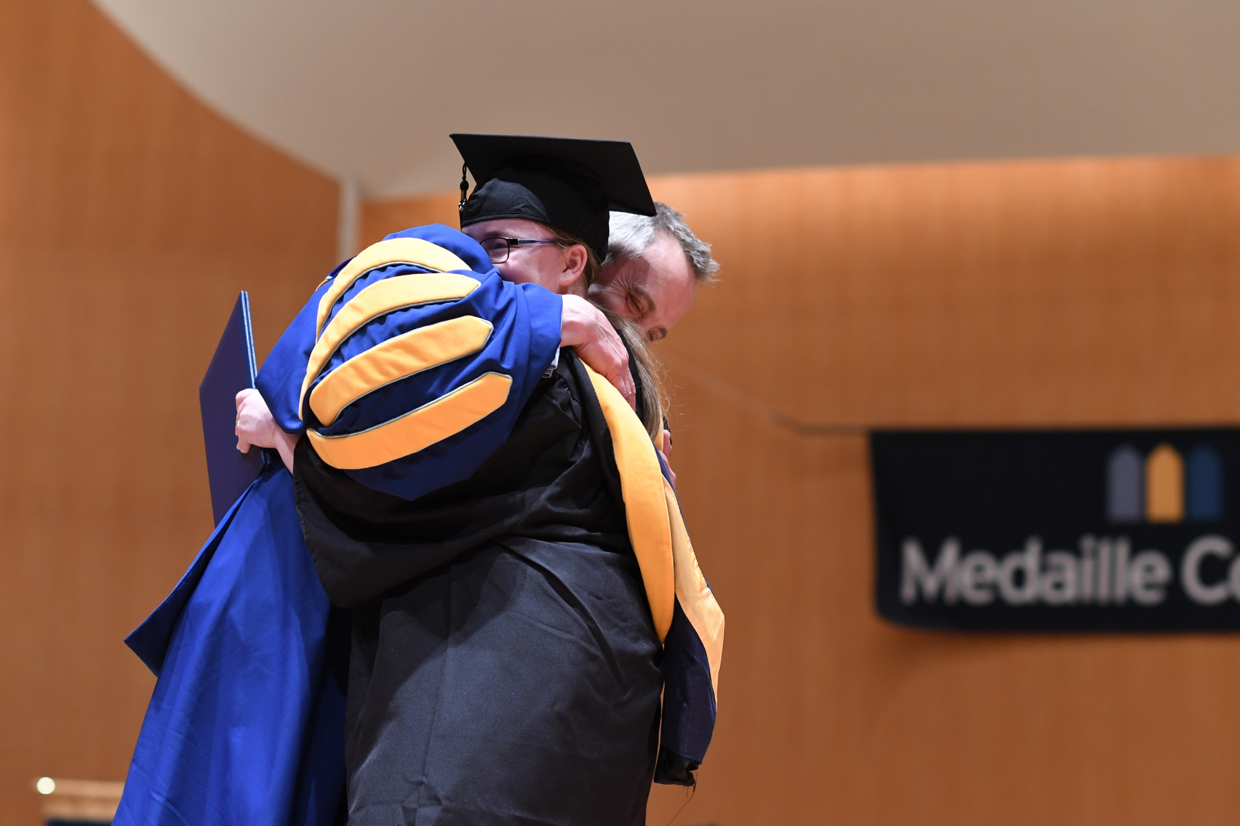 Dr. Kenneth Macur Hugging Student at Commencement